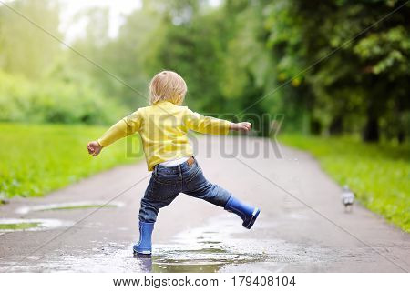 Little Boy Wearing Rain Boots Jumping In Pool Of Water