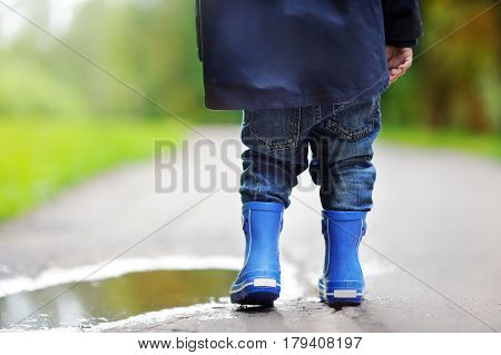 Toddler Wearing Rain Boots Standing Near A Puddle
