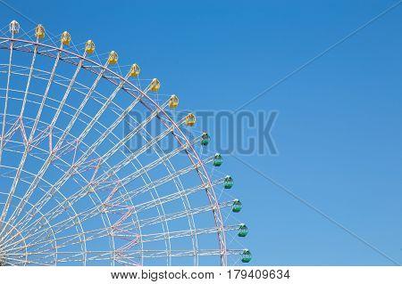 Clear blue sky over path of big ferris wheel funfair park
