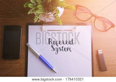 Business concept - Top view notebook writing Referral System