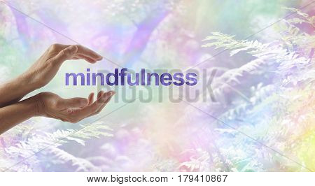 Mindfulness Meditation surrounded by surreal nature - female cupped hands with the word MINDFULNESS floating between on a rainbow bokeh woodland background and copy space