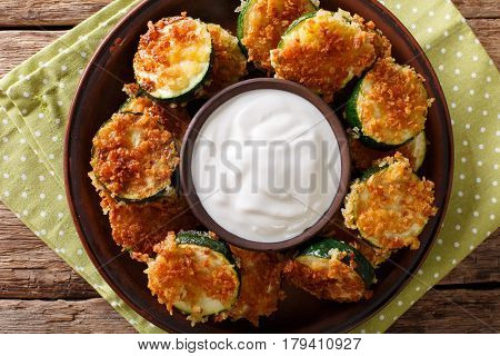 Delicious Slices Of Zucchini In Breadcrumbs With Sour Cream Close-up. Horizontal Top View