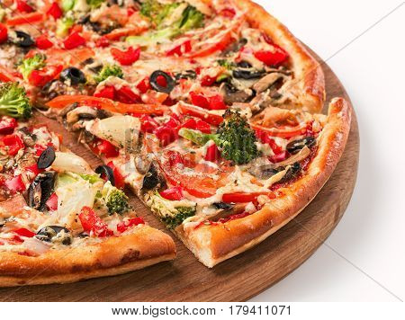 Close up view on a piece of vegetarian pizza with cauliflower, pepper, olives, onions on wooden cutting board. Isolated on white with clipping path
