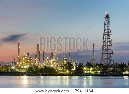 Oil refinery factory with tower during sunrise river front