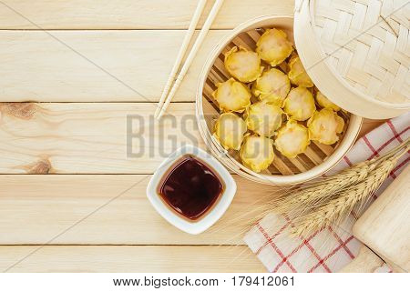 Steamed dumplings (chinese dim sum) in bamboo basket serve with chopsticks and napkin on wooden table background. Top view with copy space and text.