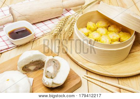 Steamed pork buns and chinese dim sum in bamboo basket serve with chopsticks and napkin on wooden table background. Closed up