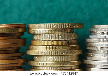 Coins stacked in three stacks can be seen against the background of green fabric