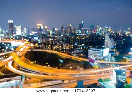 Aerial view city downtown and interchanged overpass blurred bokeh light night view abstract background