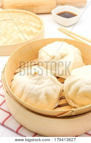 Steamed pork buns (chinese dim sum) in bamboo basket serve with chopsticks and napkin on a white background Top view with copy space and text.