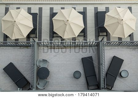 Top view of the pool chair with two empty white chairs and sunshade.