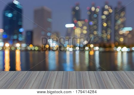 Opening wooden floor Twilight city building blurred bokeh light with reflection abstract background
