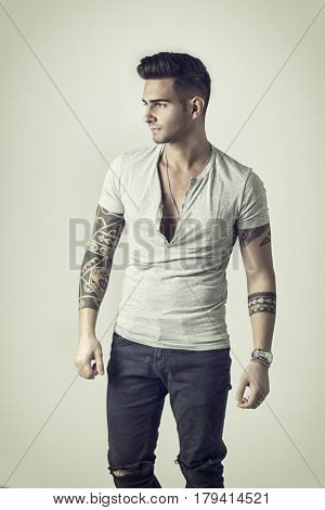 Handsome tattooed young man wearing grey t-shirt, standing against light background in studio shot