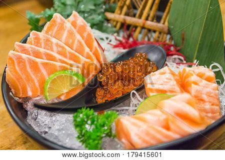 Salmon sashimi set with Salmon and Salmon caviar on big sashimi plate (Japanese food). Delicious Japanese sashimi sushi set or platter. Raw fresh Salmon meat sashimi