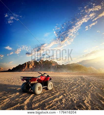 Quad bike in sand desert near mountain