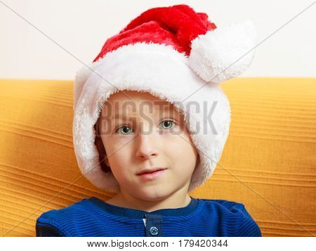 Christmassy decorations and accessories concept. Little boy sitting on sofa wearing red christmas santa claus hat