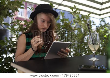 Beautiful young teen girl working on iPad in a caffe on a sunny summer day