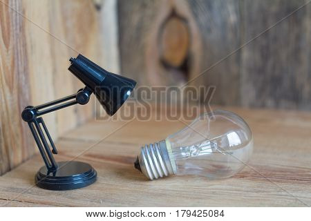 Small table lamp made of black plastic on a wooden background. Next to this child's lamp are filament lamps.