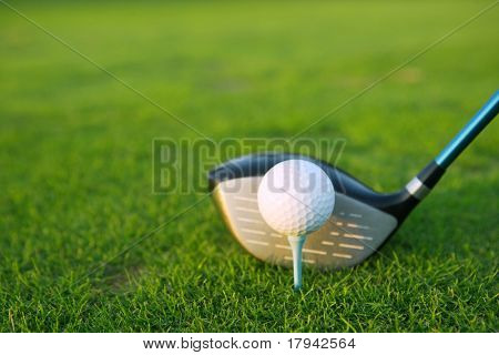 Golf tee ball club driver in green grass course closeup