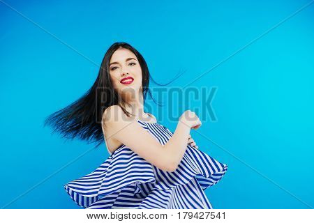 Pretty stylish girl with long hair wearing classy beautiful blue dress and posing against blue background. Fashion vogue style portrait of young happy smiling woman.