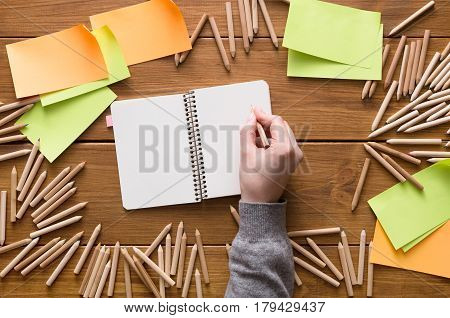 Designer drawing in sketchbook at workplace. Top view flat lay shot of many blank sticky notes, color pencils on wooden table background, copy space, nobody, objects