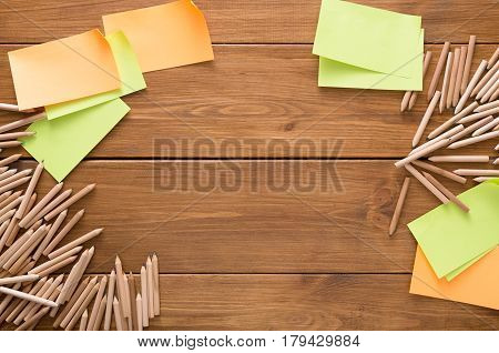 Stationery - top view of blank sticky and memo notes and color pencils made round frame on wooden table background, copy space, nobody, objects