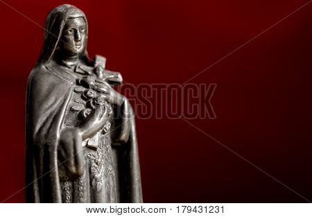 Virgin Maria metal in background red, religion