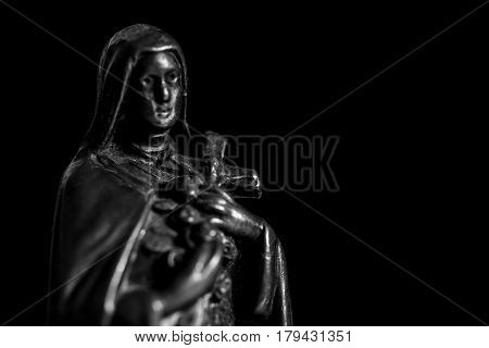 Virgin Maria metal in background black, dark