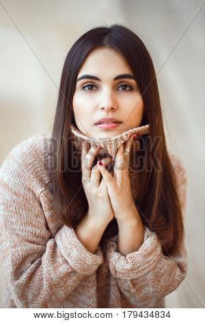 Closeup portrait of pensive white Caucasian European brunette young beautiful woman model with long dark red hair and brown eyes in turtleneck sweater looking in camera