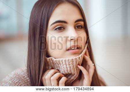 Closeup portrait of pensive white Caucasian European brunette young beautiful woman model with long dark red hair and brown eyes in turtleneck sweater looking away