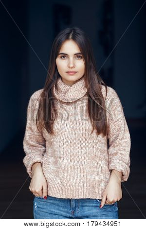 Portrait of pensive serious sad white Caucasian brunette young beautiful woman with long dark hair and brown eyes in turtleneck sweater and blue jeans indoor on black background