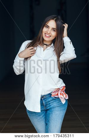 Portrait of smiling laughing white Caucasian brunette young beautiful girl woman model with long dark hair and brown eyes in white shirt and blue jeans indoor on black background