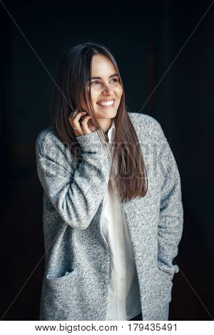 Portrait of smiling white Caucasian brunette young beautiful girl woman model with dark hair and brown eyes in white shirt and grey long coat looking in camera on black background