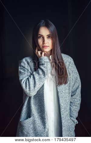 Portrait of pensive white Caucasian brunette young beautiful girl woman model with dark hair and brown eyes in white shirt and grey long coat looking in camera on black background