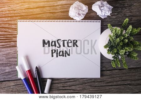 Master Plan Word With Notepad And Green Plant On Wooden Background.