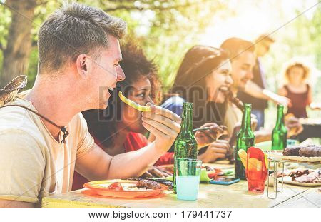 Happy friends doing barbecue on summer day in backyard home garden - Young cheerful people eating tasty meat bbq dinner - Concept about positive mood - Focus on left blond man face - Warm filter