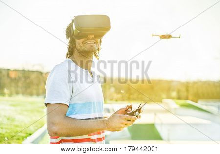 Young man using a drone with remote controller wearing virtual reality glasses making photos and videos - Young guy having fun with new technology trends - Focus on face headset - Warm filter