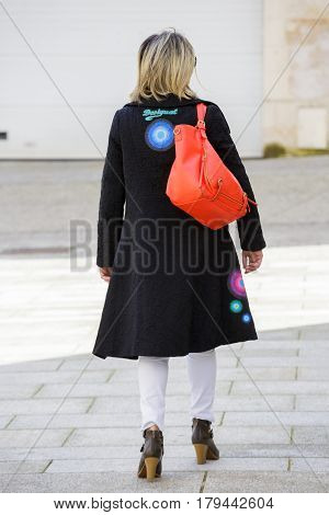 Paris France - March 27 2017: Back view of a well dressed blond woman walking on the city streets