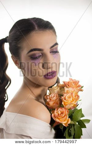 Young girl with artistic make up and yellow roses