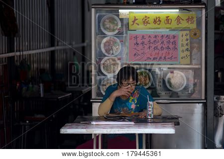 Malacca Malaysia 25/09/2016 Elderly Asian woman sat at Chinese hawker restaurant table reading with soft drink with hawker stall in the background.