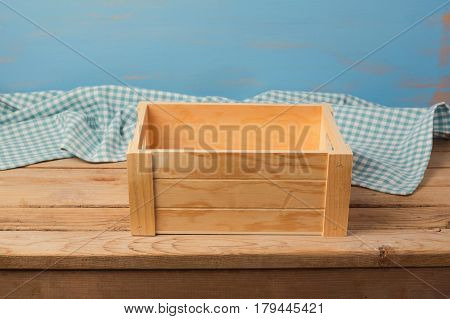 Empty wooden box on table with checked tablecloth for product montage display