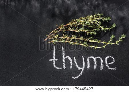 Fresh bunch of thyme on a chalky black board with a name top view with a chalk dark style