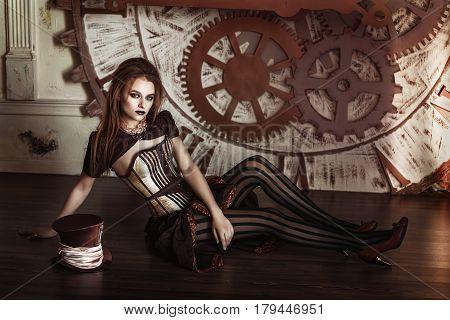Portrait of a beautiful steampunk woman near big clock