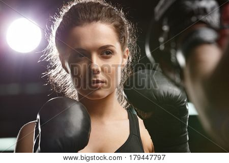 Photo of concentrated young strong sports lady boxer make exercises in gym with man trainer and looking aside.
