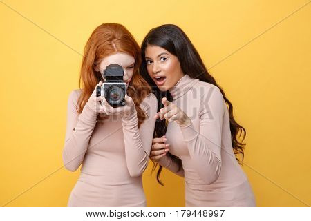 Picture of cheerful young african woman pointing to camera while her friend redhead lady photographing over yellow background.