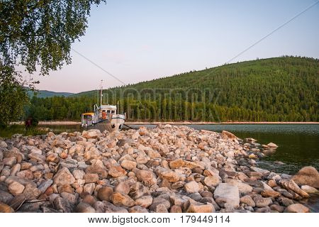 Scenic view of Baikal lake with colorful stones on the bank and a boat on the background