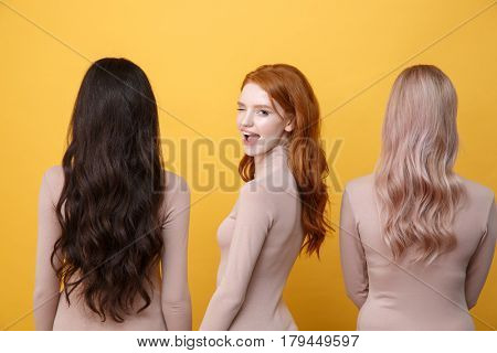 Back view image of young three ladies standing over yellow background. Redhead happy lady winking to camera.