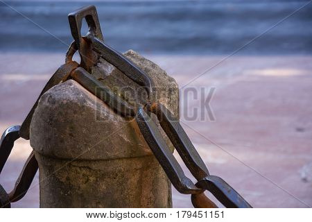 Photo of a bollard with chain, selective focus and sunlight