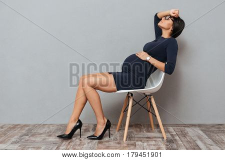 Image of bored pregnant business woman sitting over grey background. Eyes closed.