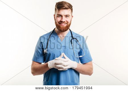 Portrait of a smiling happy male medical doctor or nurse wearing surgical gloves and looking at camera isolated on white background
