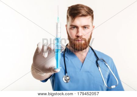 Close up portrait of a serious surgeon holding a syringe isolated on white background